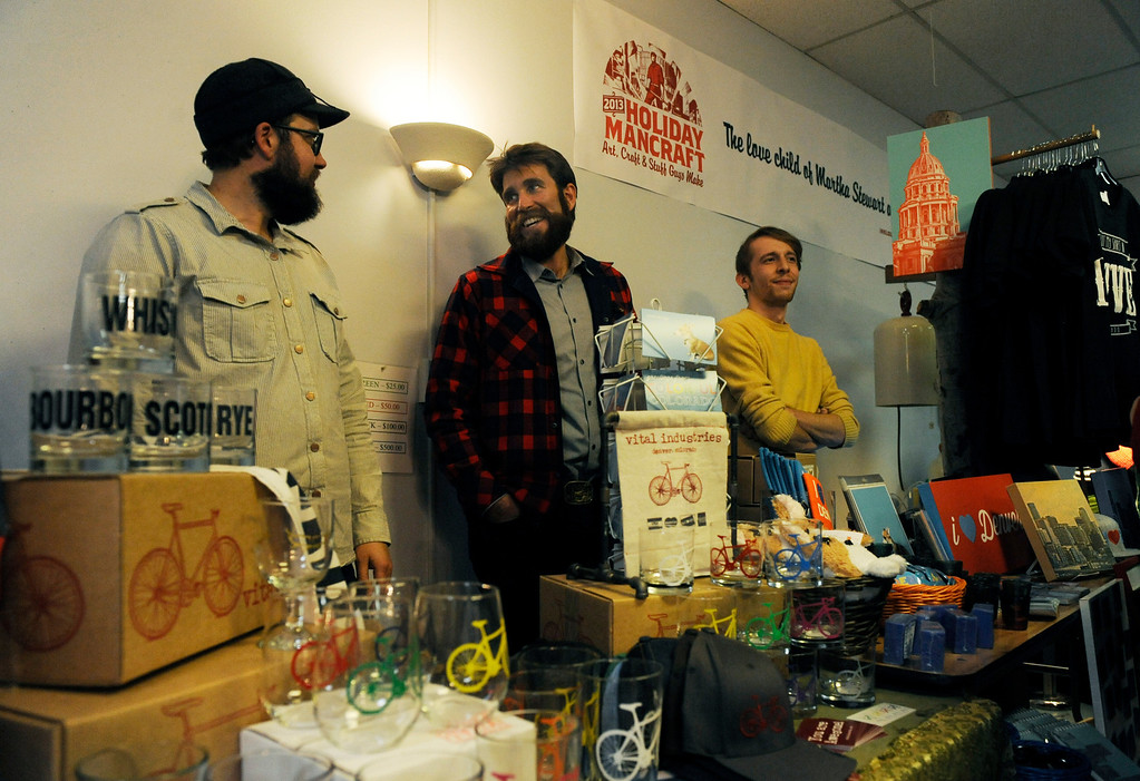 . Brett Childs, left to right, Samuel Schimek and Brent Senft display their artwork and other crafts on Dec. 6 at the Holiday Mancraft 2013 craft fair at the VFW Post in Denver, Colo., where over 40 vendors showcased their goods, drank cocktails and beer, and competed in a mustache contest. Photo by Jamie Cotten, Special to The Denver Post