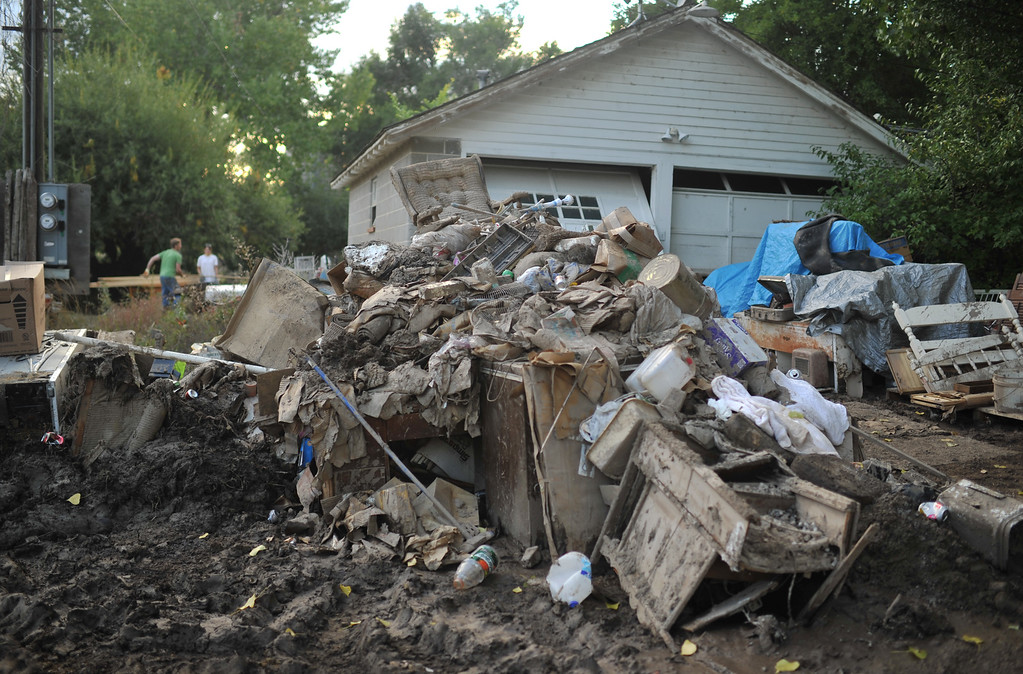 . Dan Williams, left, and his wife Jenna are moving debris out from their house. Williams Farm in Hygiene is damaged by flood water. September 21, 2013. (Photo by Hyoung Chang/The Denver Post)