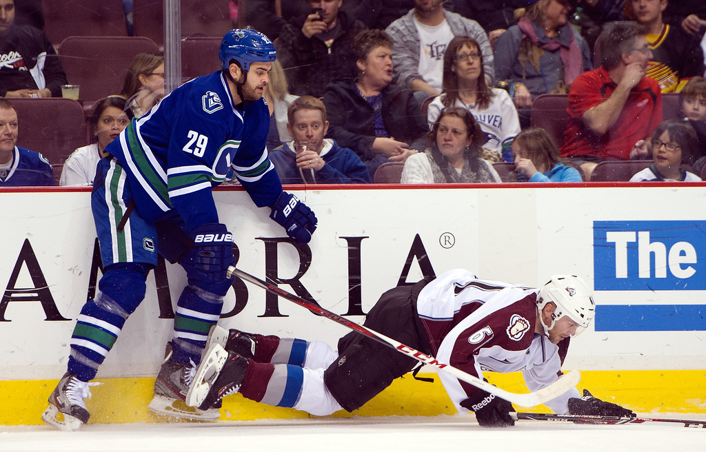 . Tom Sestito #29 of the Vancouver Canucks knocks down Erik Johnson #6 of the Colorado Avalanche along the side boards during the first period in NHL action on April 10, 2014 at Rogers Arena in Vancouver, British Columbia, Canada.  (Photo by Rich Lam/Getty Images)