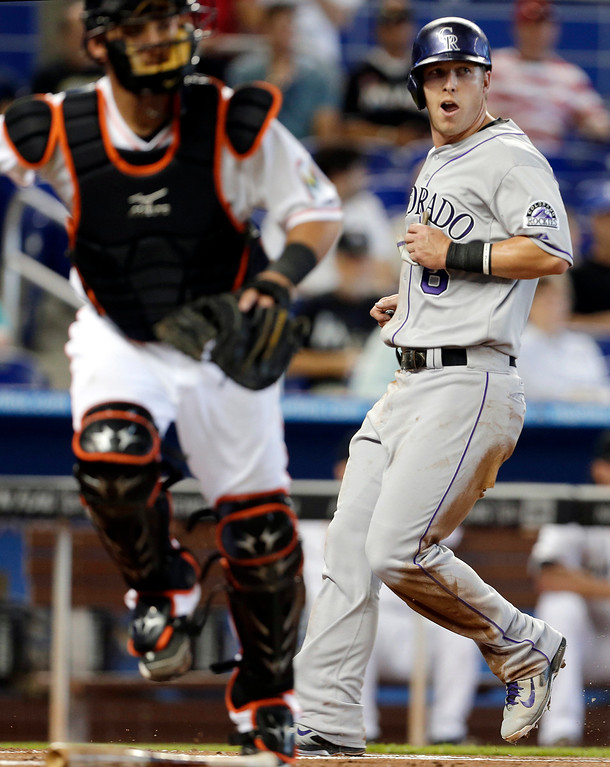 . Colorado Rockies\' Corey Dickerson (6) scores on a ground out by Michael Cuddyer in the first inning of a baseball game against the Miami Marlins, Thursday, April 3, 2014, in Miami. At left is Miami Marlins catcher Jeff Mathis. (AP Photo/Lynne Sladky)