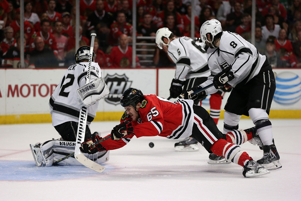 . Andrew Shaw #65 of the Chicago Blackhawks gets checked by Drew Doughty #8 from behind while taking a shot on Jonathan Quick #32 of the Los Angeles Kings during Game Seven of the Western Conference Final in the 2014 Stanley Cup Playoffs at United Center on June 1, 2014 in Chicago, Illinois.  (Photo by Jonathan Daniel/Getty Images)