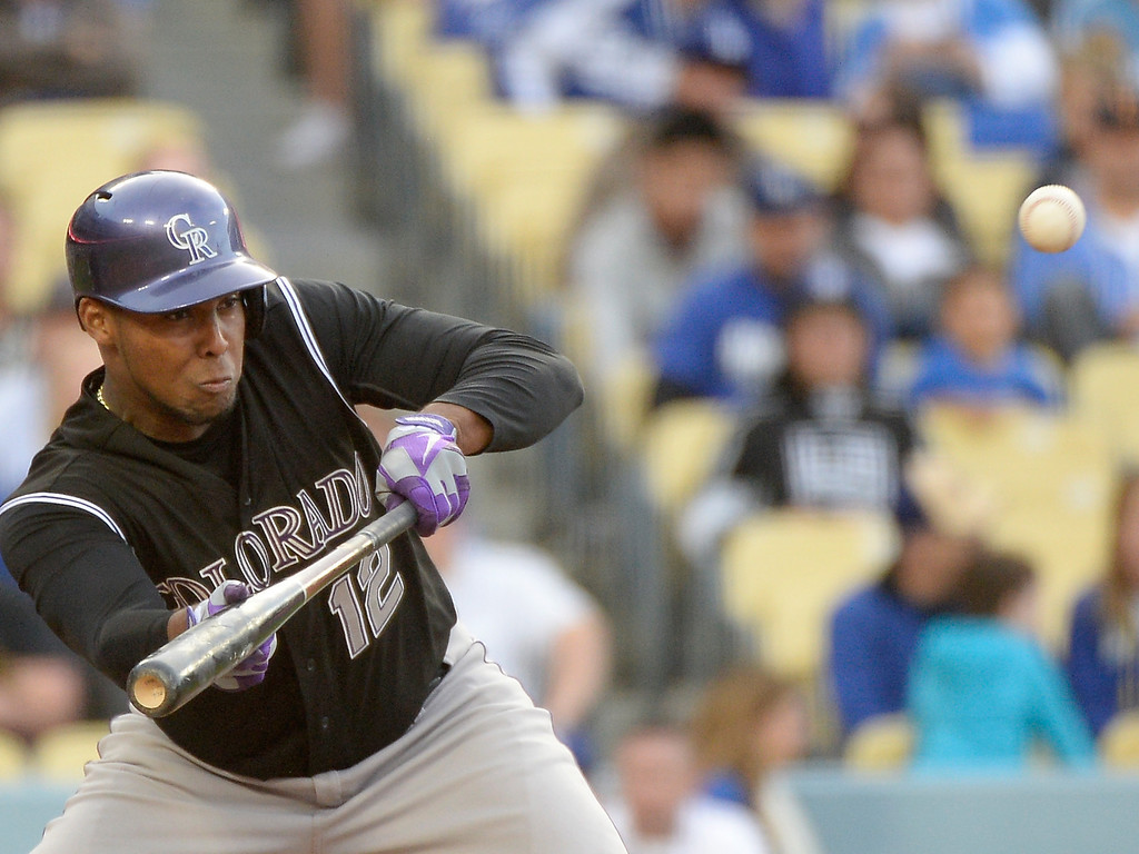 . LOS ANGELES, CA - APRIL 26:  Juan Nicasio #12 of the Colorado Rockies bunts in the third inning against the Los Angeles Dodgers at Dodger Stadium on April 26, 2014 in Los Angeles, California.  (Photo by Harry How/Getty Images)