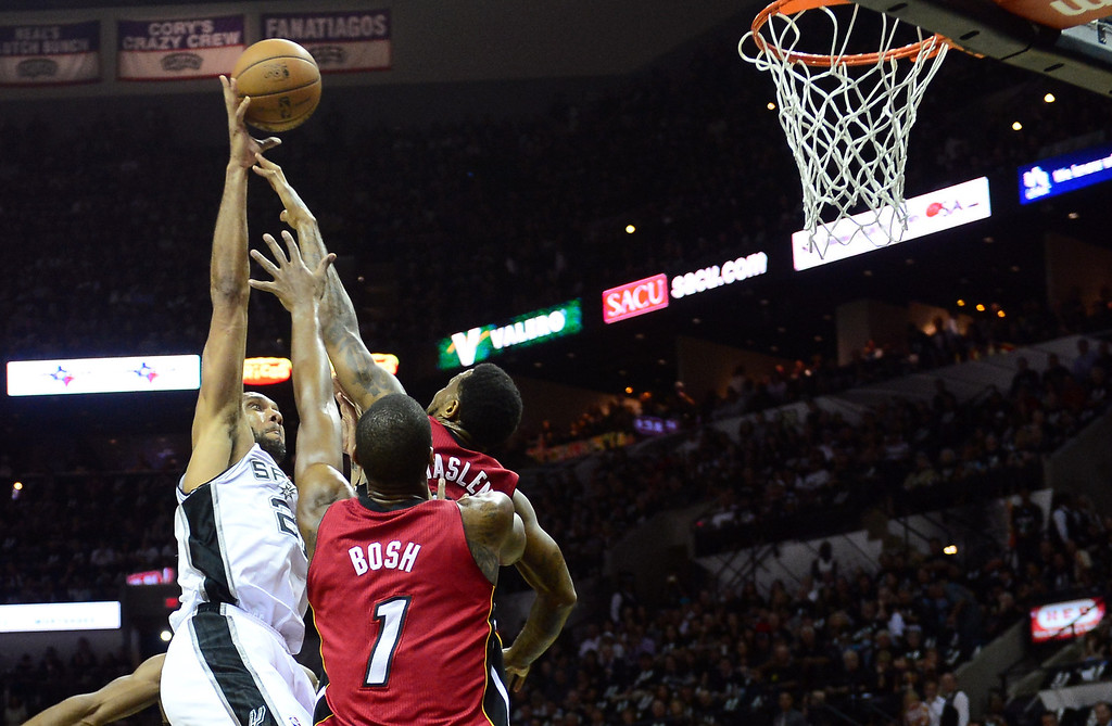 . Tim Duncan (L)of the San Antonio Spurs shoots under pressure from Udonis Haslem (R) and Chris Bosh (C) of the Miami Heat during Game 3 of the NBA Finals on June 11, 2013 in San Antonio, Texas.    FREDERIC J. BROWN/AFP/Getty Images