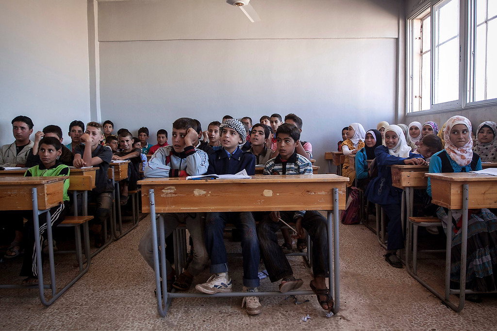 . In this Thursday, Sept. 26, 2013 photo, Syrian children sit in their classroom in a public school in Madaya village as classes begin in the Idlib province countryside of Syria. Millions of Syrian children most of them in government-controlled areas have returned to school in the past two weeks, despite the conflict that according to UNICEF has left 4,000 Syrian schools or one in five damaged, destroyed or sheltering displaced families. (AP Photo)