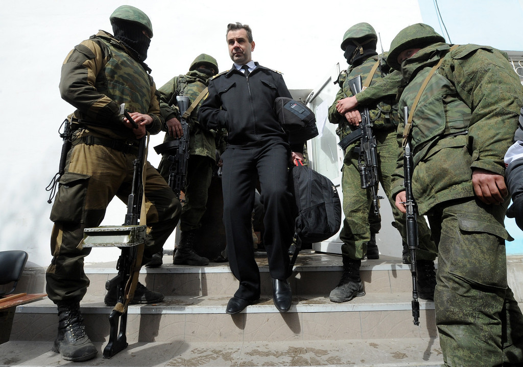 ". An Ukrainian officer leaves as Russian soldiers patrol at the Ukrainian navy headquarters in the Crimean city of Sevastopol on March 19, 2014.  Pro-Russian forces captured Ukraine\'s naval commander after seizing his headquarters in Crimea on Wednesday as Moscow\'s grip tightened on the peninsula despite Western warnings its ""annexation\"" would not go unpunished. AFP PHOTO/  VIKTOR DRACHEV/AFP/Getty Images"