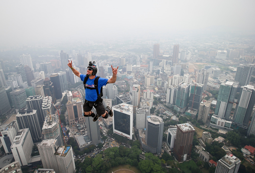 . Base jumper Kieran Francis Tomlinson of Australia leaps from the 300-meter Open Deck of the Malaysia\'s landmark Kuala Lumpur Tower during the International Tower Jump in Kuala Lumpur, Friday, Sept. 27, 2013.  (AP Photo/Vincent Thian)