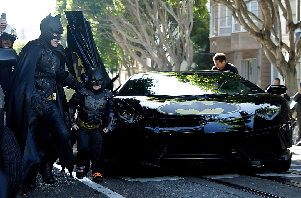 """. Miles Scott, dressed as Batkid, second from left, exits the Batmobile with Batman to save a damsel in distress in San Francisco, Friday, Nov. 15, 2013.  San Francisco turned into Gotham City on Friday, as city officials helped fulfill Scott\'s wish to be \""""Batkid.\"""" Scott, a leukemia patient from Tulelake in far Northern California, was called into service on Friday morning by San Francisco Police Chief Greg Suhr to help fight crime, The Greater Bay Area Make-A-Wish Foundation says. (AP Photo/Jeff Chiu)"""