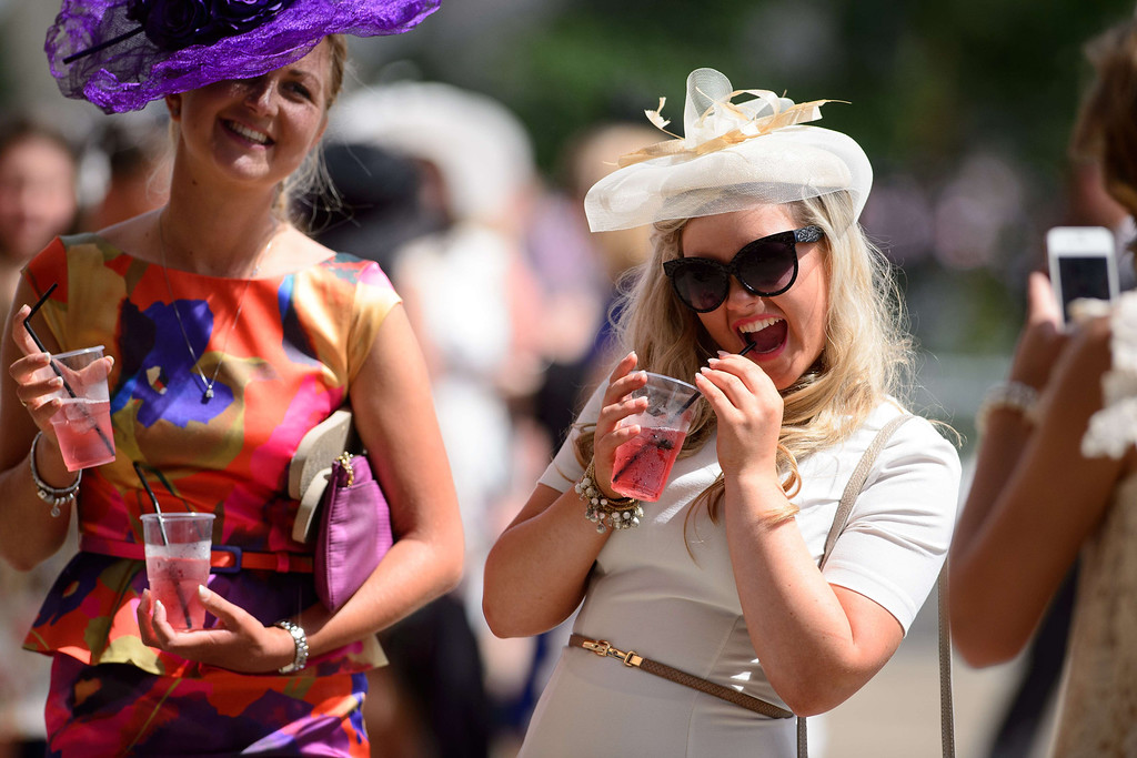 . Racegoers enjoy the sun on the second day of the Royal Ascot horse racing meet, in Berkshire, west of London, on June 18, 2014. AFP PHOTO / LEON NEAL/AFP/Getty Images