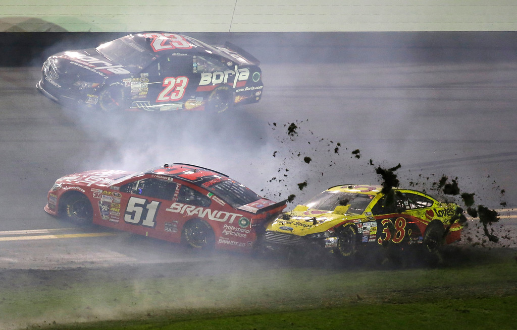 . Justin Allgaier (51) and David Gilliland (38) are involved in a crash as Alex Bowman (23) drives past during the NASCAR Daytona 500 Sprint Cup series auto race at Daytona International Speedway in Daytona Beach, Fla., Sunday, Feb. 23, 2014. (AP Photo/John Raoux)