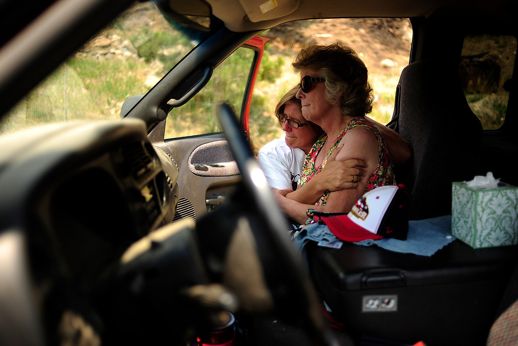 . Deanna Skelton is consoled by her daughter, Lucinda Able, as they seen their burned ranch during the family\'s first trip back to their burned home on Sunday, July 1, 2012. AAron Ontiveroz, The Denver Post