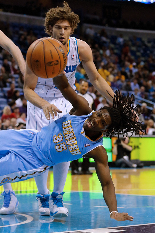 . Denver Nuggets forward Kenneth Faried (35) falls while reaching for a rebound in front of New Orleans Hornets center Robin Lopez (15) in the first half of an NBA basketball game in New Orleans, Monday, March 25, 2013. (AP Photo/Bill Haber)