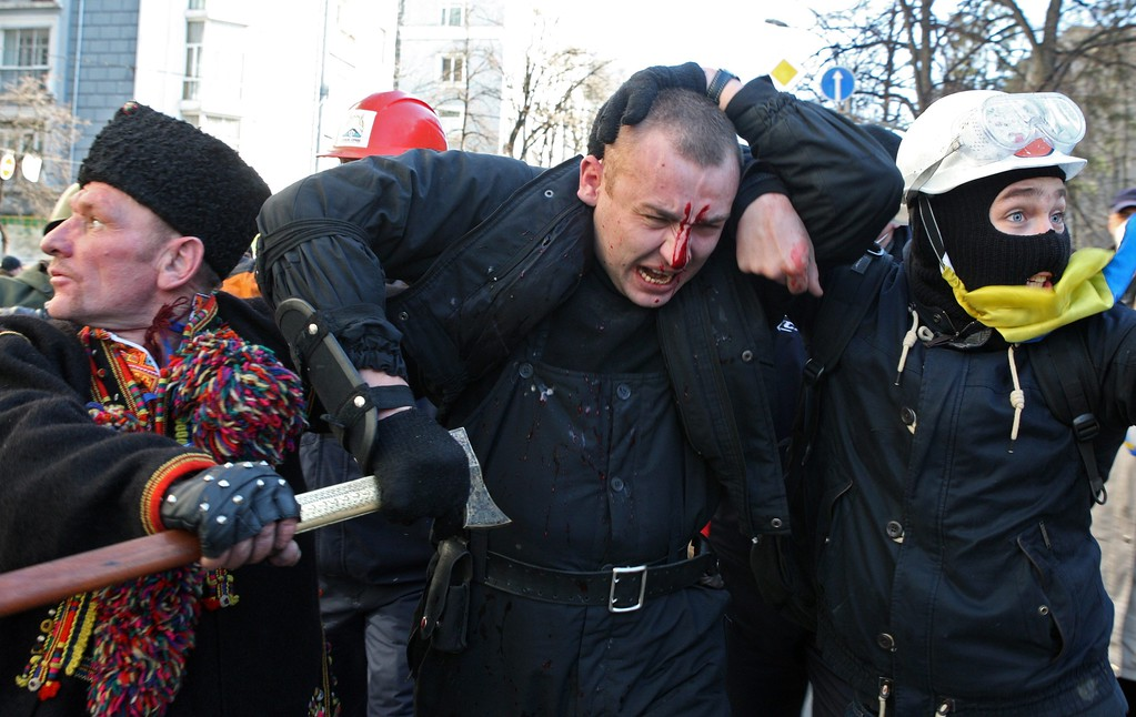 . Protesters escort injured policeman during an anti-government protest in downtown Kiev, Ukraine, 18 February 2014.   EPA/IGOR KOVALENKO