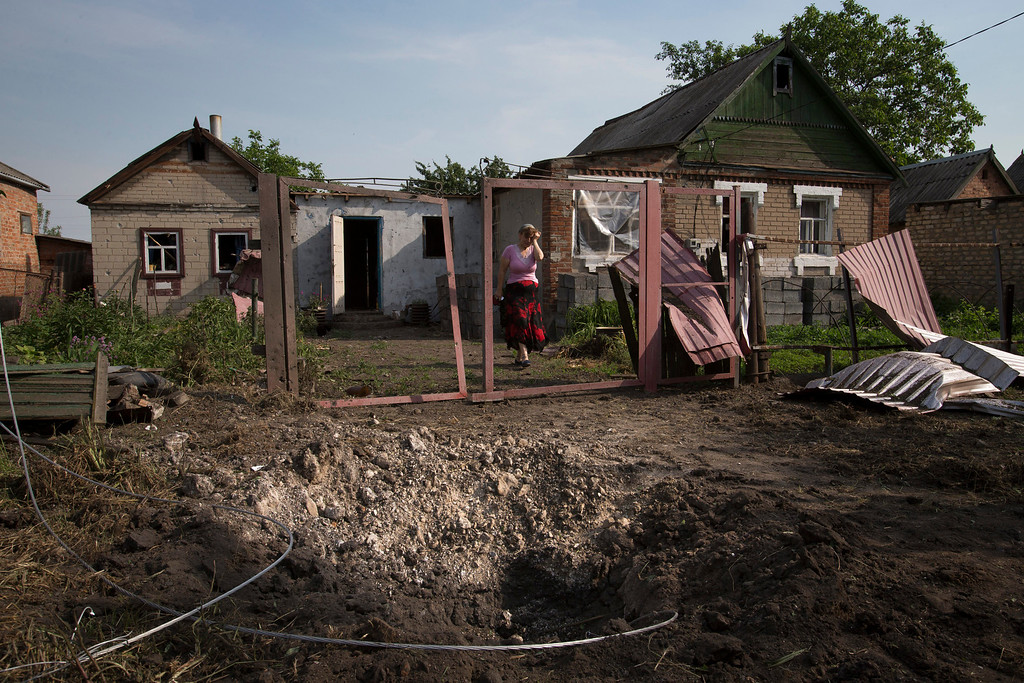 . Mizan Mazasheva, a local citizen, walks next to her destroyed house after a mortar bomb, foreground, landed following an attack from Ukrainian government forces in Semyonovka village near the major highway which links Kharkiv, outside Slovyansk, Ukraine, Friday, May 23, 2014.  (AP Photo/Alexander Zemlianichenko)