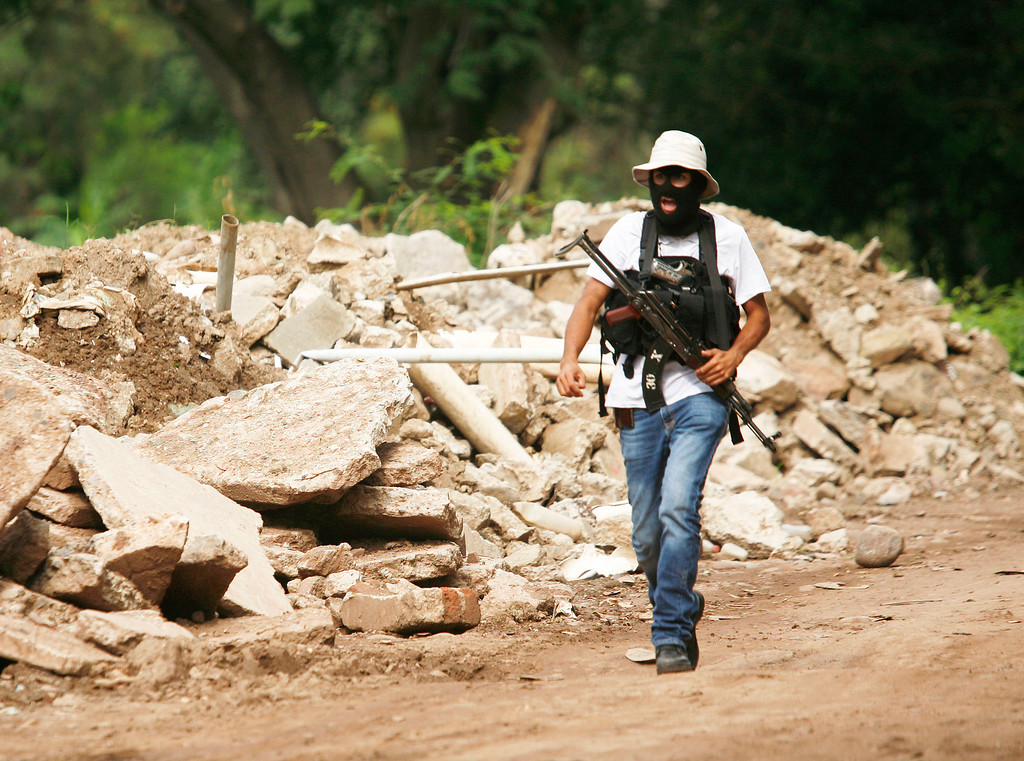 . A masked and armed member of a recently formed self-defense group walks in a dirt road at the entrance to the town of Aguililla, Mexico, Wednesday, July 24, 2013. Mexico\'s rough western state of Michoacan is proving just as tough a thorn in the side of President Enrique Pena Nieto as it was for his predecessor after gunmen believed to be working for the Knights Templar cartel launched a coordinated series of a half-dozen ambushes on federal police convoys last Tuesday and another self-defense group has sprung up to fight against the Knights Templar.(AP Photo/Gustavo Aguado)
