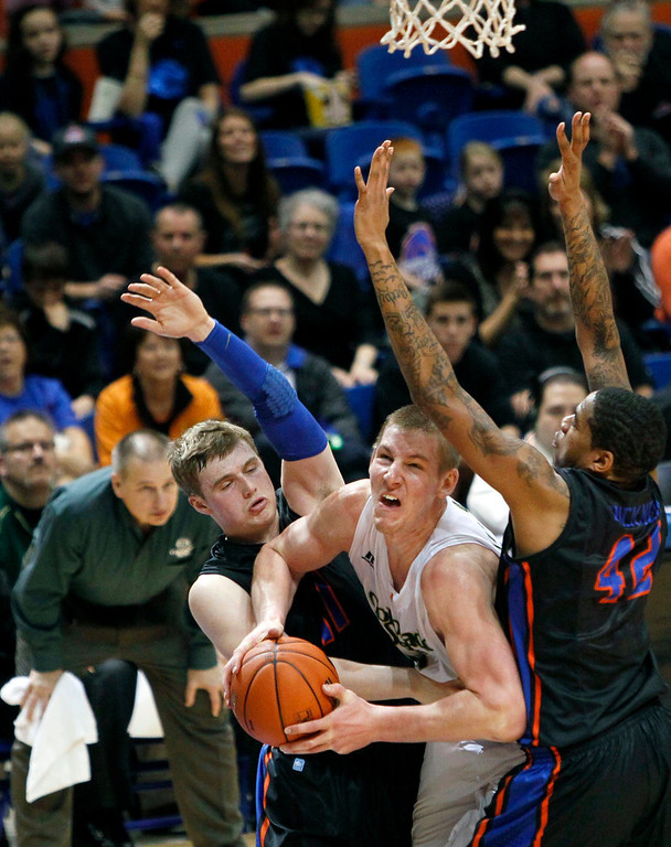 . Colorado State center Colton Iverson (45) drives against Boise State defenders Jeff Elorriaga (11) and Kenny Buckner (42) during an NCAA college basketball game in Boise, Idaho, Saturday, March 2, 2013.  (AP Photo/Darin Oswald)