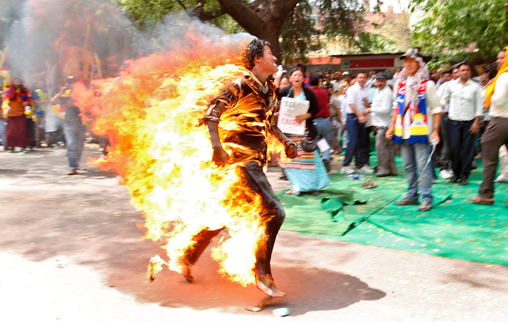 . A Tibetan exile runs after setting himself on fire during a protest against the upcoming visit of Chinese President Hu Jintao to India in New Delhi March 26, 2012. Hu is scheduled to attend the BRICS (Brazil, Russia, India, China and South Africa) Summit in India on March 29. REUTERS/Stringer