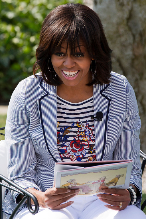 """. First lady Michelle Obama smiles before reading the book \""""Cloudy With A Chance of Meatballs\"""" as part of the annual White House Easter Egg Roll, Monday, April 1, 2013,  on the South Lawn of the White House in Washington. (AP Photo/Jacquelyn Martin)"""