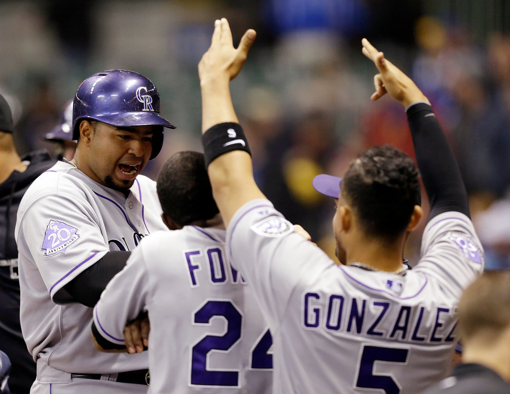 . Colorado Rockies\' Wilin Rosario, left, reacts after his two-run home run against the Milwaukee Brewers during the second inning of a baseball game, Wednesday, April 3, 2013, in Milwaukee. (AP Photo/Jeffrey Phelps)