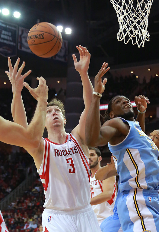 . Houston Rockets center Omer Asik (3) and Denver Nuggets forward Kenneth Faried look for a rebound during the first half of an NBA basketball game in Houston on Sunday, April 6, 2014. (AP Photo/Richard Carson)