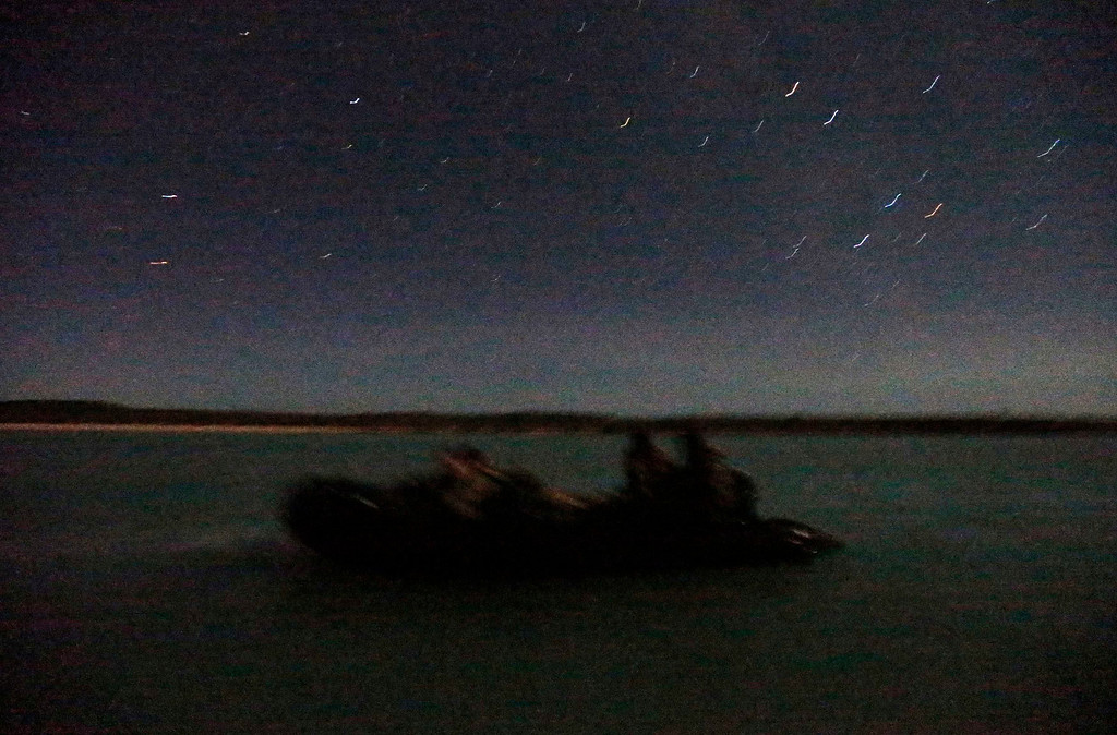 . Soldiers from Australia\'s North West Mobile Force (NORFORCE) unit are lit by moonlight as they sit aboard an inflatable boat searching for a suitable landing point off Astell Island, part of the English Company Islands, inside Arnhem Land in the Northern Territory, Australia July 16, 2013. NORFORCE is a surveillance unit that employs ancient Aboriginal skills to help in the seemingly impossible task of patrolling the country\'s vast northwest coast. NORFORCE\'s area of operations is about 1.8 million square km (700,000 square miles), covering the Northern Territory and the north of Western Australia. Aboriginal reservists make up a large proportion of the 600-strong unit, and bring to bear their knowledge of the land and the food it can provide. Fish, shellfish, turtle eggs and even insects supplement rations during the patrol, which is on the lookout for illegal foreign fishing vessels and drug smugglers, as well as people smugglers from neighboring Indonesia. Picture taken July 16, 2013. REUTERS/David Gray