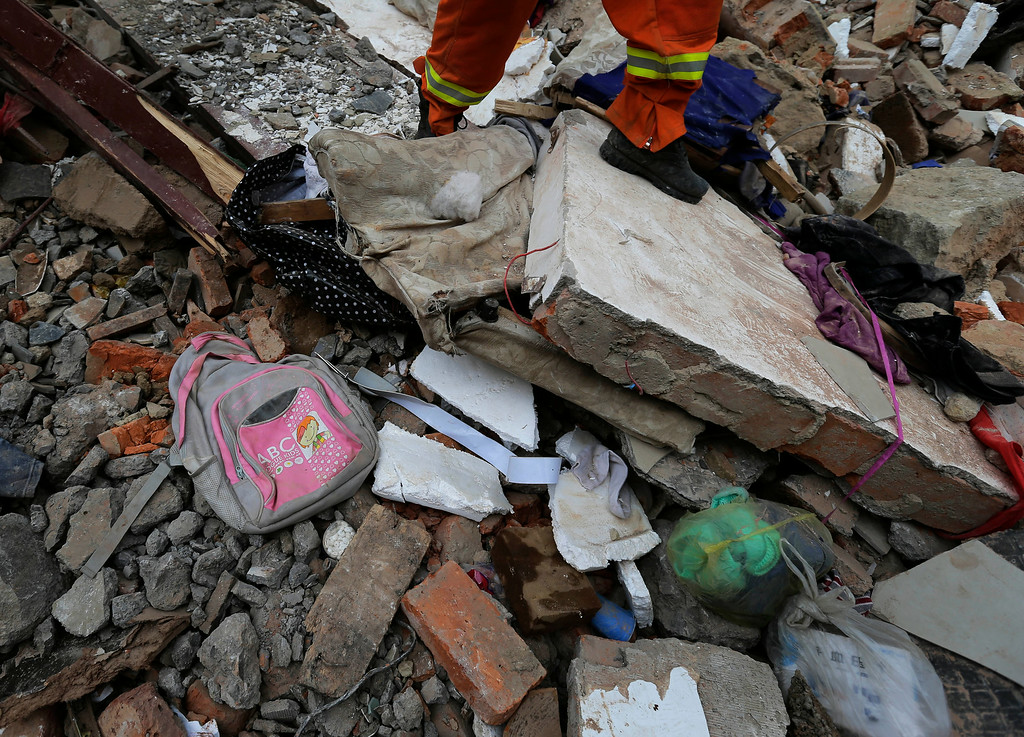 . A rescuer walks past a school bag and other items laying on the rubbles of destroyed houses following a massive earthquake in the town of Longtoushan in Ludian County in southwest China\'s Yunnan Province Tuesday, Aug. 5, 2014. (AP Photo/Andy Wong)