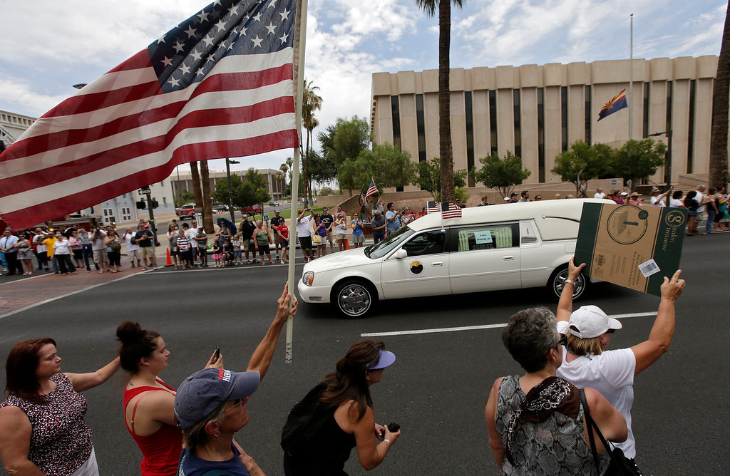 . A procession of 19 hearses drives through Phoenix, Sunday, July 7, 2013. The 19 Hotshot firefighters were carried in procession in separate hearses from Phoenix to Prescott, Ariz. They had been killed fighting a wildfire about a week ago.  (AP Photo/Chris Carlson)
