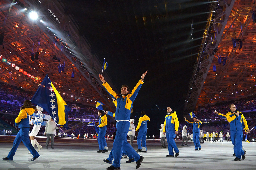 . Bosnia and Herzegovina\'s flag bearer, alpine skier Zana Novakovic leads her national delegation during the Opening Ceremony of the Sochi Winter Olympics at the Fisht Olympic Stadium on February 7, 2014 in Sochi.  AFP PHOTO / ALBERTO PIZZOLI/AFP/Getty Images