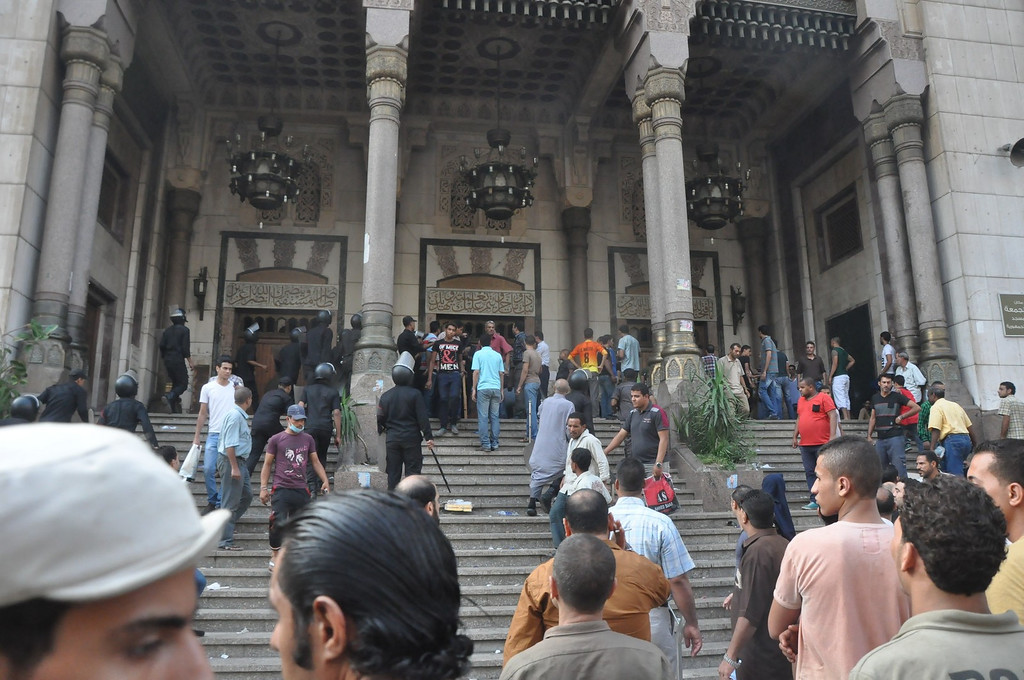 . A group of Egyptians gather at the al-Fatah mosque, after hundreds of Muslim Brotherhood supporters barricaded themselves inside the mosque overnight, following a day of fierce street battles that left scores of people dead, near Ramses Square in downtown Cairo, Egypt, Saturday, Aug. 17, 2013. Authorities say police in Cairo are negotiating with people barricaded in a mosque and promising them safe passage if they leave. Muslim Brotherhood supporters of Egypt\'s ousted Islamist president are vowing to defy a state of emergency with new protests today, adding to the tension. (AP Photo/Hussein Tallal)