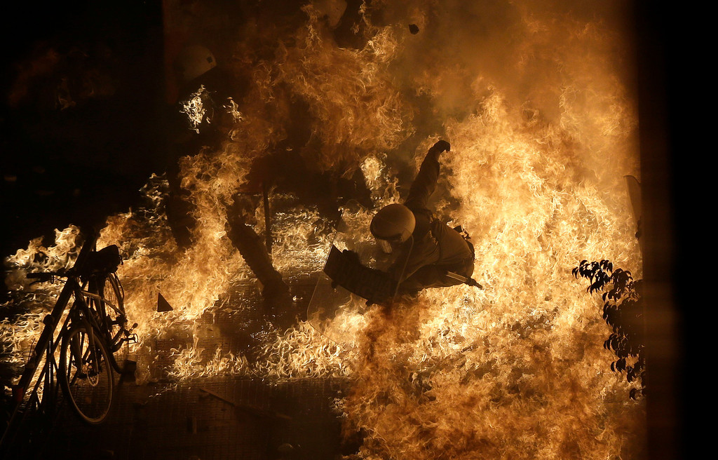 . In this Nov. 7, 2012 file photo, a riot police officer is engulfed by petrol bomb flames thrown by protesters in front of the parliament during clashes in Athens. (AP Photo/Dimitri Messinis, File)