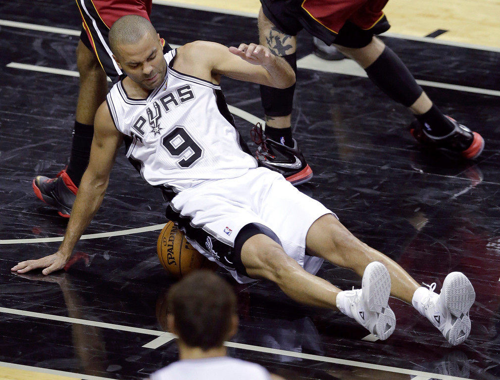 . San Antonio Spurs guard Tony Parker (9) lands on the ball against the Miami Heat during the first half in Game 1 of the NBA basketball finals on Thursday, June 5, 2014, in San Antonio. (AP Photo/Tony Gutierrez)