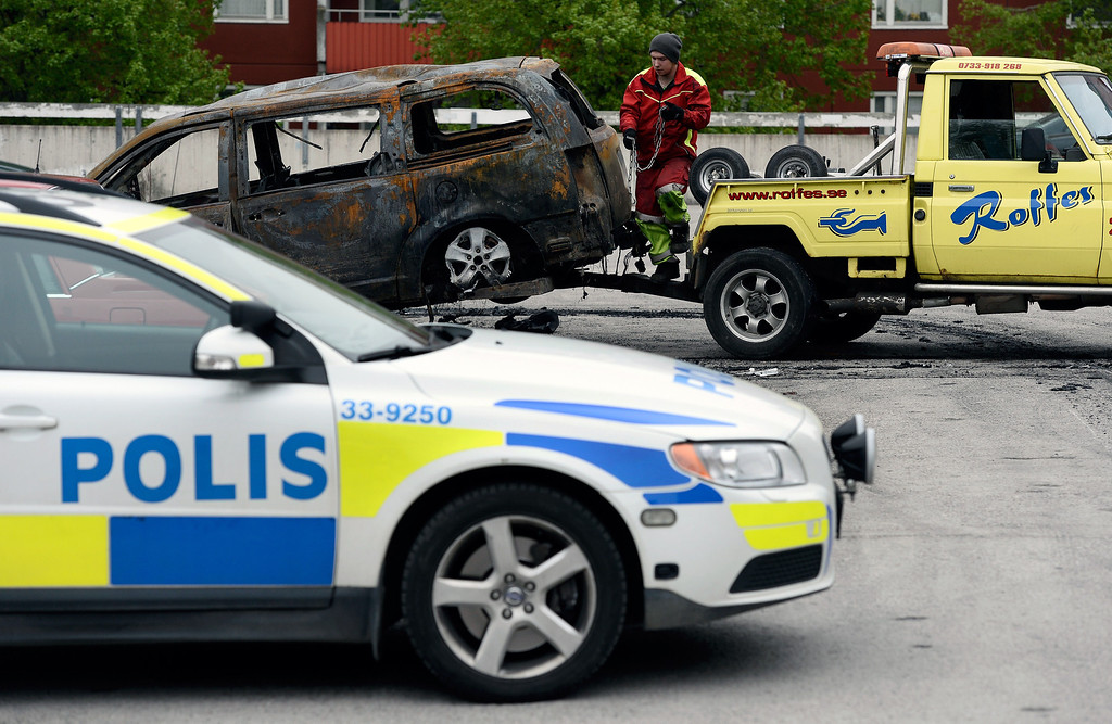 . A burned-out van is prepared for removal after youths rioted in Husby, northern Stockholm on May 21, 2013. Youths in the immigrant-heavy Stockholm suburb of Husby torched cars and threw rocks at police, in riots believed to be linked to the deadly police shooting of a local resident. An apartment building had to be evacuated for an hour during the night after fire spread inside a garage, and shops and schools in the low-income neighbourhood had their windows crashed. JONATHAN NACKSTRAND/AFP/Getty Images