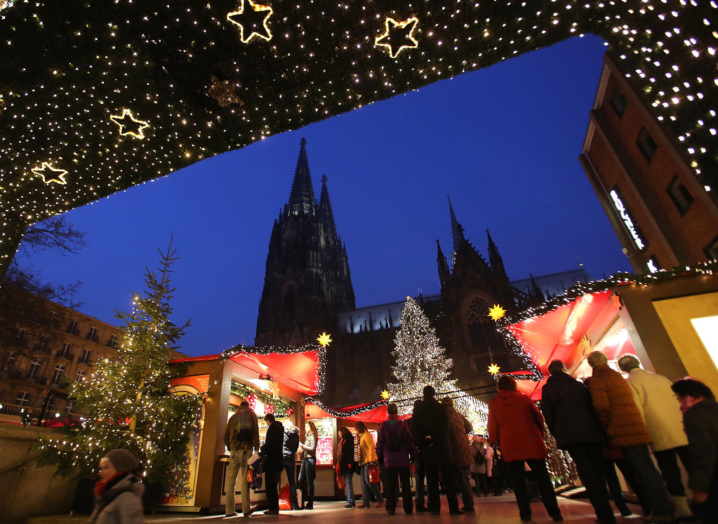 . Visitors enjoy a stroll at the Christmas  market in front of the Cologne  Cathedral , in Cologne, western Germany, Tuesday Nov. 26, 2013.  (AP Photo/dpa, Oliver Berg)