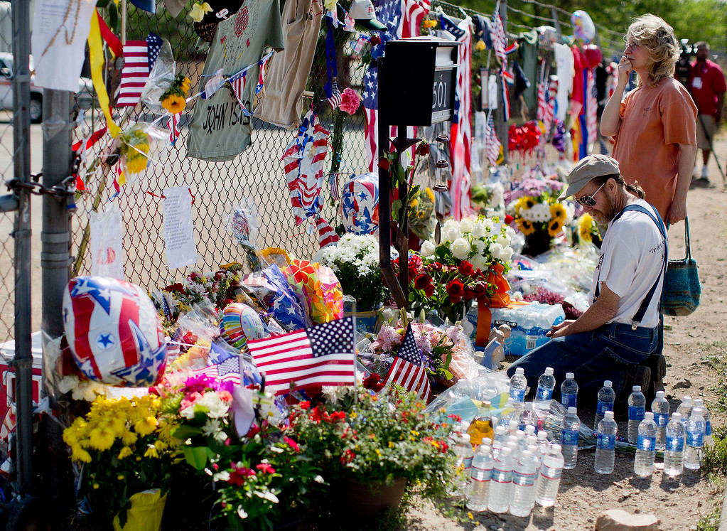 . Stephen and Cheri Grady visit a memorial along the fence outside the Granite Mountain Interagency Hotshot Crew fire station, Tuesday, July 2, 2013 in Prescott, Ariz.  (AP Photo/Julie Jacobson)