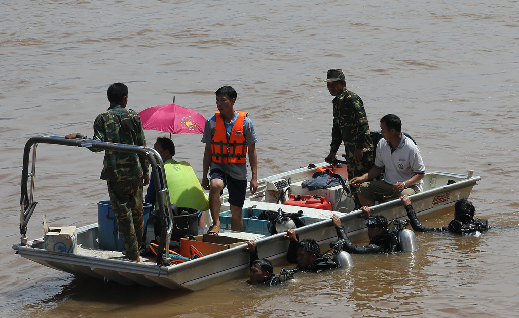 . Divers cling to a boat as they search for bodies of victims of a crashed Lao Airlines plane in the Mekong River, Pakse, Laos Thursday, Oct. 17, 2013. Rescuers in fishing boats pulled bodies from the muddy river as officials in Laos ruled out finding survivors from a plane that crashed in stormy weather, killing 49 people from 11 countries. (AP Photo/sakchai Lalit)