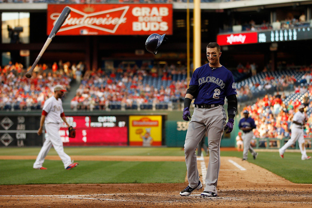 . Colorado Rockies\' Troy Tulowitzki, right, tosses his bat and helmet after striking out against Philadelphia Phillies relief pitcher Mike Adams to end the seventh inning of a baseball game, Monday, May 26, 2014, in Philadelphia. Philadelphia won 9-0. (AP Photo/Matt Slocum)