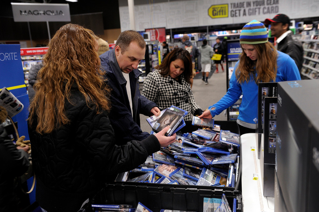 . Shoppers lookd through a bin of movies on sale Thursday night, November 28, 2013 at the Best Buy store in Lone Tree. Many metro area stores got a jump on Black Friday by opening on Thursday. Best Buy remained open all night. Photo By Karl Gehring/The Denver Post