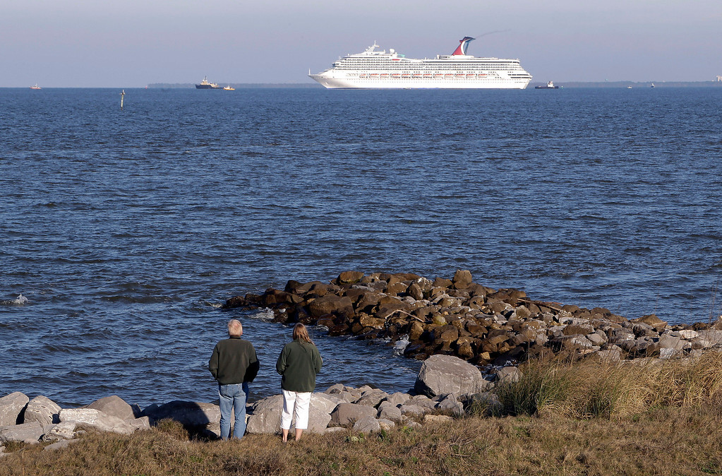 . People watch the cruise ship Carnival Triumph as it is towed into Mobile Bay from Dauphin Island, Ala., Thursday, Feb. 14, 2013. (AP Photo/Dave Martin)
