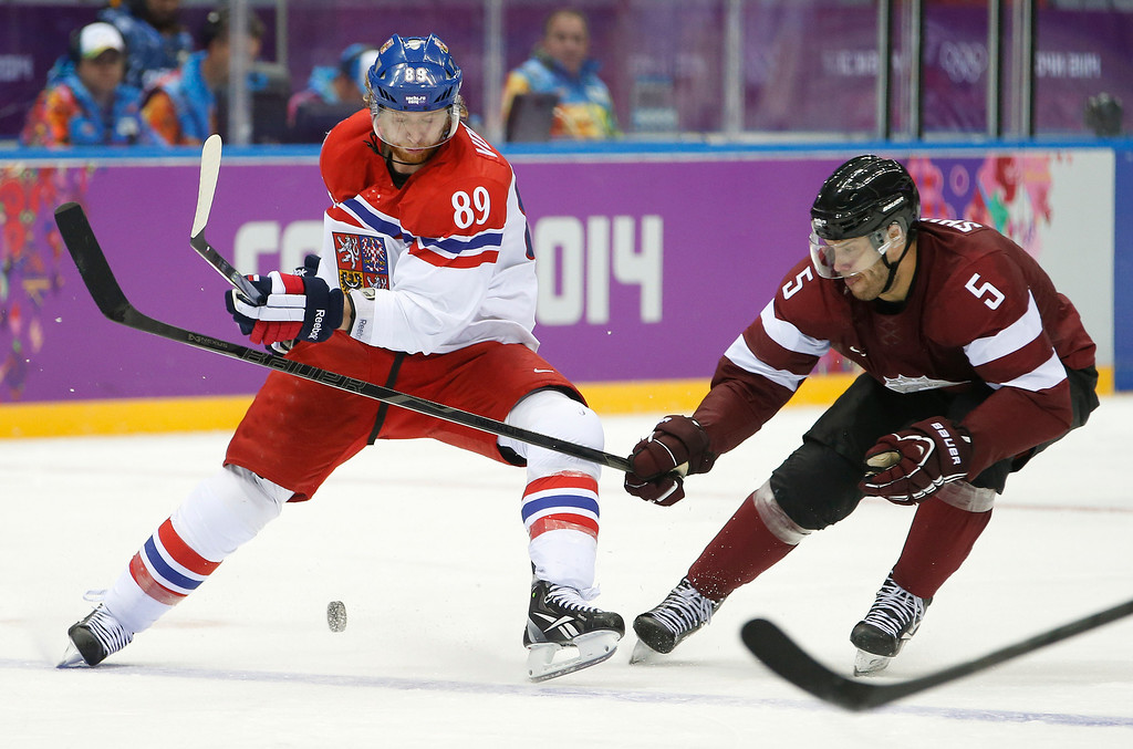 . Czech Republic forward Jakub Voracek, left, and Latvia forward Janis Sprukts battle for the puck in the third period of a men\'s ice hockey game at the 2014 Winter Olympics, Friday, Feb. 14, 2014, in Sochi, Russia. (AP Photo/Mark Humphrey)