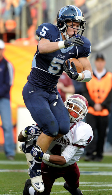 . Valor Christian\'s Christian McCaffrey (5) dives for a few more yards in the grasp of Anthony Murray (4). Cherokee Trail High School takes on Valor Christian High School in the 5A Colorado State Football Championships at Sports Authority Field at Mile High in Denver on Saturday, Dec. 1, 2012. Kathryn Scott Osler, The Denver Post