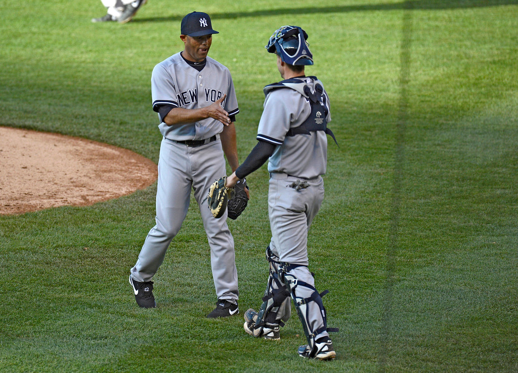 . Mariano Rivera (42) of the New York Yankees shakes hands with Chris Stewart after recording his 621st save by closing out the Colorado Rockies May 9, 2013 at Coors Field. The Yankees defeated the Rockies 3-1. (Photo By John Leyba/The Denver Post)