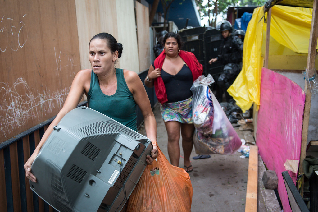. Squatters who were occupying an abandoned lot leave carrying their belongings after being evicted by police in Rio de Janeiro, Brazil, on April 11, 2014. The lot, owned by a telephone company, included offices and warehouses and was occupied last week. AFP PHOTO/YASUYOSHI CHIBAYASUYOSHI CHIBA/AFP/Getty Images
