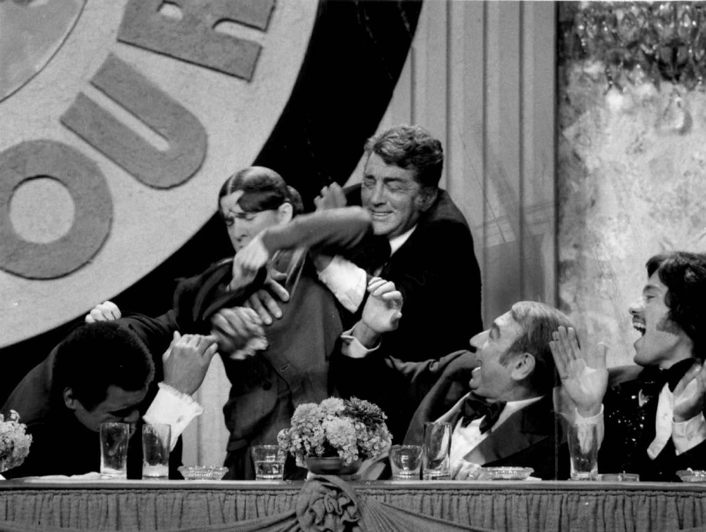 . What is this-a roast or a beating? Ruth Buzzi attacks Muhammad Ali, left, with her purse as host Dean Martin tries to rescue the heavyweight champion, in an NBC roast 1976. Howard Cosell, right, joins the fun, along with Freddie Prinze, Gene Kelly, Wilt Chamberlain, Floyd Patterson and Orson Welles. 1976.  Denver post Library Archive