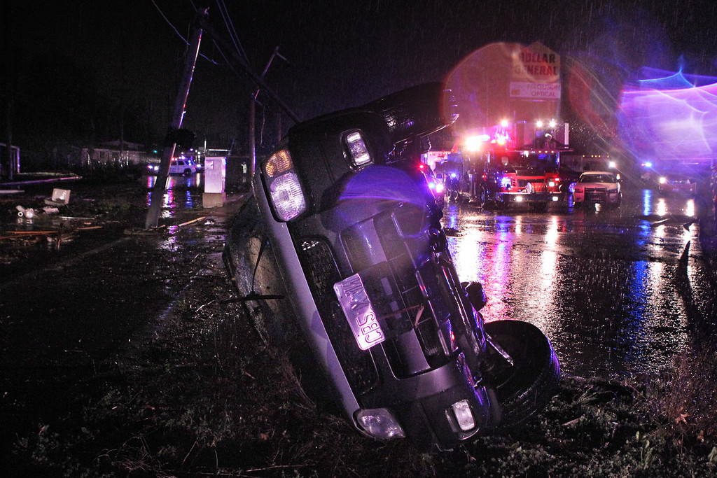 . A car lies on its side in the plaza next to Howdershell Road and Lynn Haven Lane following a strong spring storm in Hazelwood late Wednesday evening, April 10, 2013.   (AP Photo/Erik M. Lunsford, Post-Dispatch)
