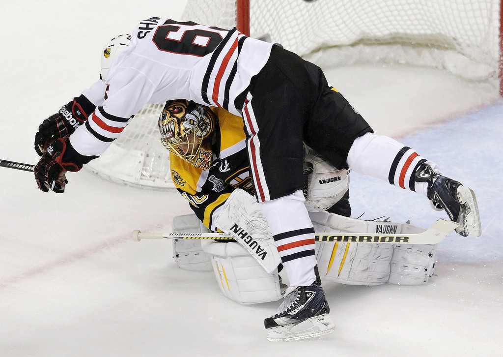 . Chicago Blackhawks center Andrew Shaw (65) collides with Boston Bruins goalie Tuukka Rask, underneath, of Finland,during the first period in Game 3 of the NHL hockey Stanley Cup Finals in Boston, Monday, June 17, 2013. (AP Photo/Charles Krupa)