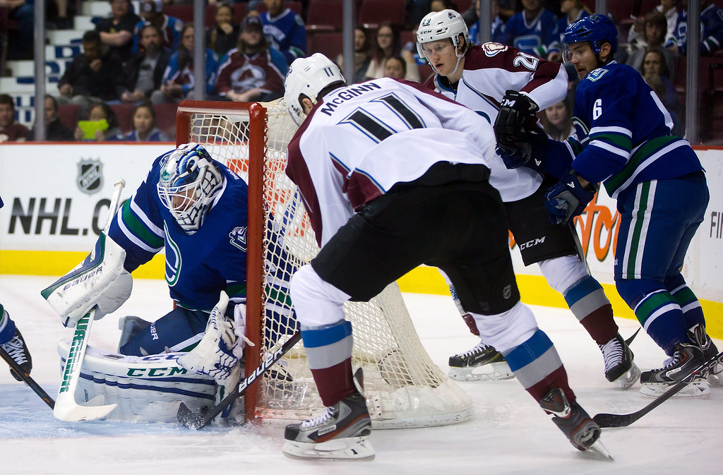 . Vancouver Canucks goalie Jacob Markstrom, left, of Sweden, stops Colorado Avalanche\'s Jamie McGinn (11) as Nathan MacKinnon (29) and Canucks\' Yannick Weber, right, of Switzerland, watch during the first period of an NHL hockey game Thursday, April 10, 2014, in Vancouver, British Columbia. (AP Photo/The Canadian Press, Darryl Dyck)