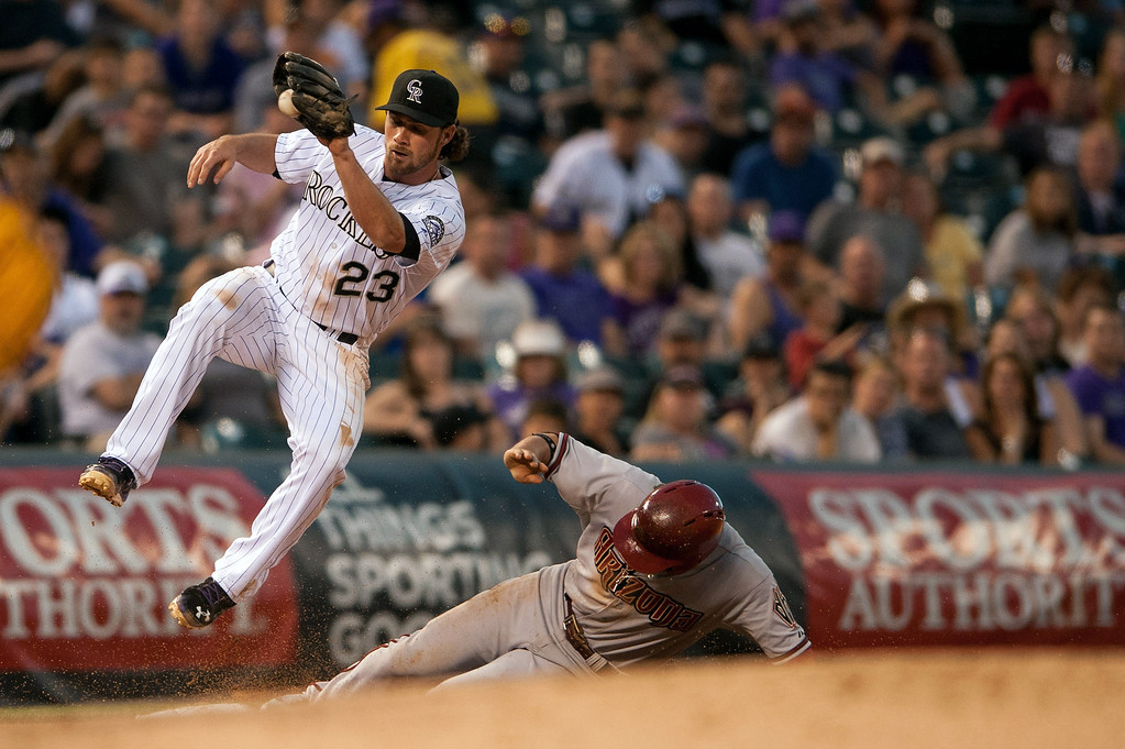 . Charlie Culberson #23 of the Colorado Rockies leaps to catch the throw but is late to apply the tag as Martin Prado #14 of the Arizona Diamondbacks steals third base at Coors Field on June 3, 2014 in Denver, Colorado.  The Diamondbacks beat the Rockies 4-2. (Photo by Dustin Bradford/Getty Images)