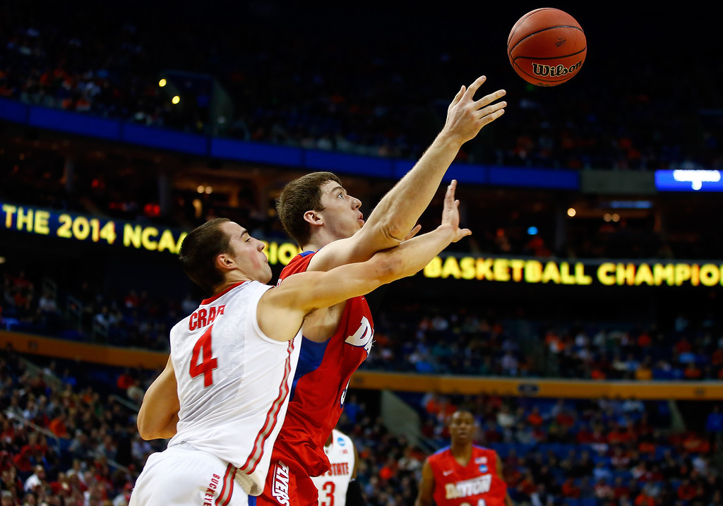 . Matt Kavanaugh #35 of the Dayton Flyers and Aaron Craft #4 of the Ohio State Buckeyes battle for a loose ball during the second round of the 2014 NCAA Men\'s Basketball Tournament at the First Niagara Center on March 20, 2014 in Buffalo, New York.  (Photo by Jared Wickerham/Getty Images)