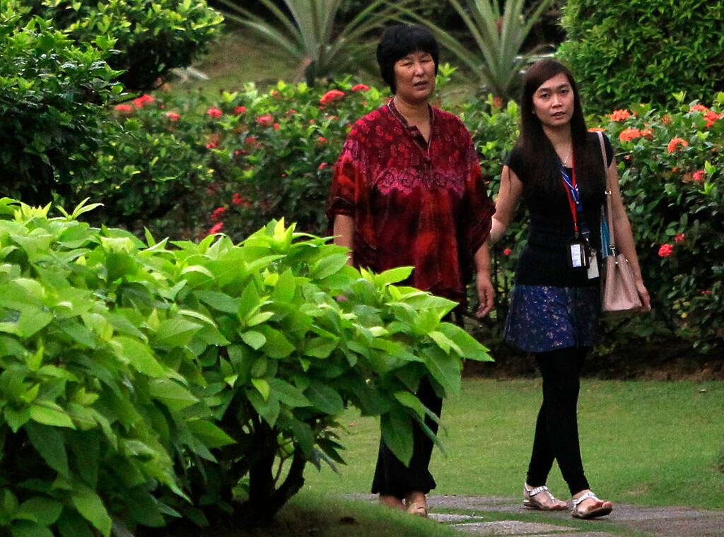 . A Chinese relative, left, of passengers aboard a missing Malaysia Airlines plane, walks with a counselor at a resort in Cyberjaya, Malaysia, Thursday, March 20, 2014. Military search planes flew over a remote part of the Indian Ocean on Thursday hunting for debris in ìprobably the best leadî so far in finding the missing Malaysia Airlines flight, officials said. (AP Photo/Lai Seng Sin)