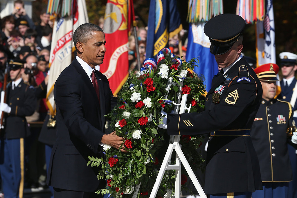. U.S. President Barack Obama (L) positions a commemorative wreath during a ceremony on Veterans Day at the Tomb of the Unknowns at Arlington National Cemetery on November 11, 2013 in Arlington, Virginia. For Veterans Day, President Obama is paying tribute to military veterans past and present who have served and sacrificed their lives for their country.  (Photo by Mark Wilson/Getty Images)