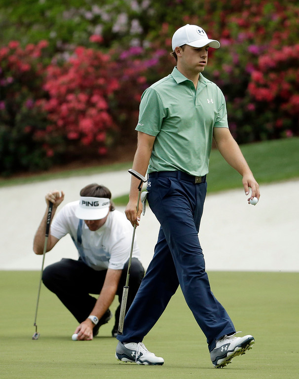 . Bubba Watson, left, lines up his putt as Jordan Spieth walks off the 13th green during the fourth round of the Masters golf tournament Sunday, April 13, 2014, in Augusta, Ga. (AP Photo/Chris Carlson)